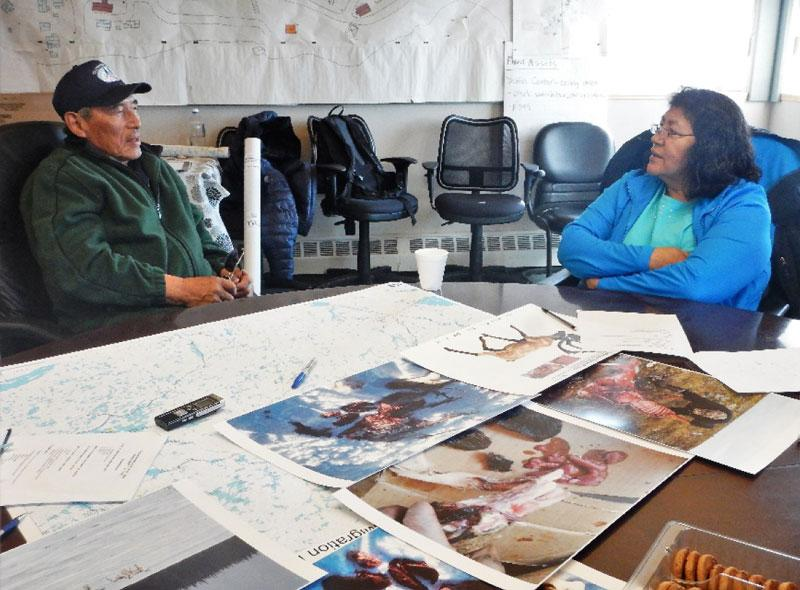 Researcher Rita Wetrade interviewing elder Jimmy Kodzin, Wekweètì, May 12th, 2015. Notice the use of photo-voice and maps.